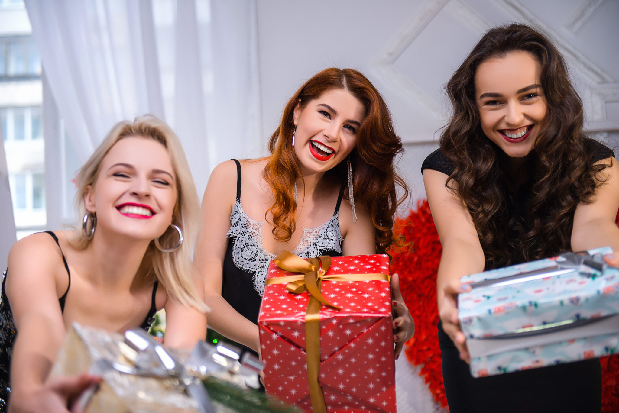 Девичник в студии, 3 девушки в платьях протягивающие фотографу подарочные коробки