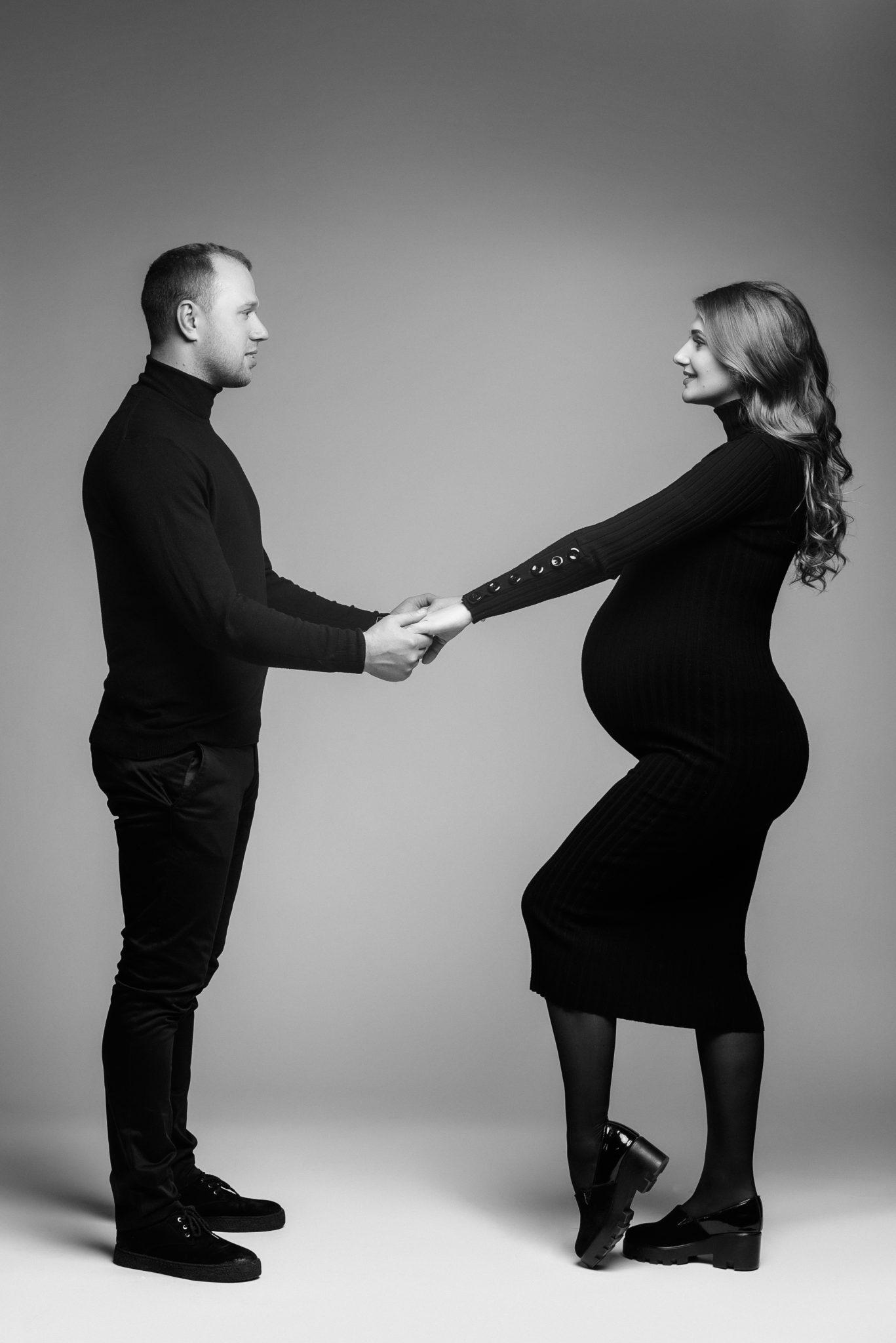 Портфолио фотосессии беременности в студии, беременная девушка с мужем стоят боком на сером фоне, ЧБ фотография