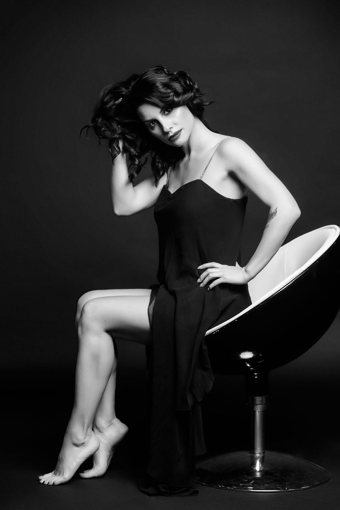 Фотосессия Премиум, чб, модель, девушка в платье, на черном фоне сидит в черно-белом кресле