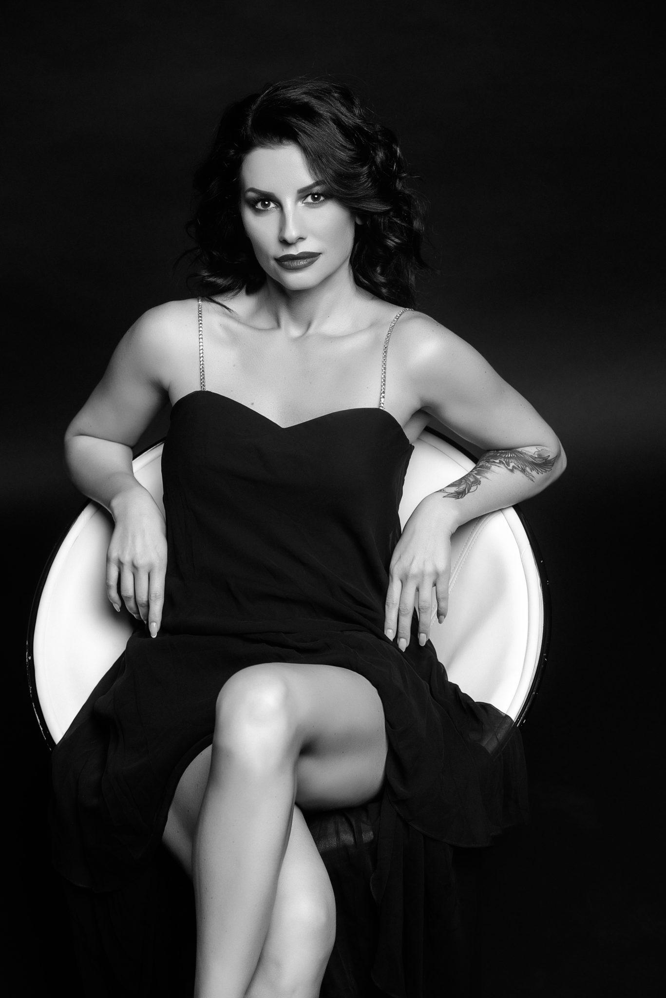 Фотосессия Премиум, чб, модель, девушка в платье, на черном фоне сидит в черно-белом кресле лицом к фотографу