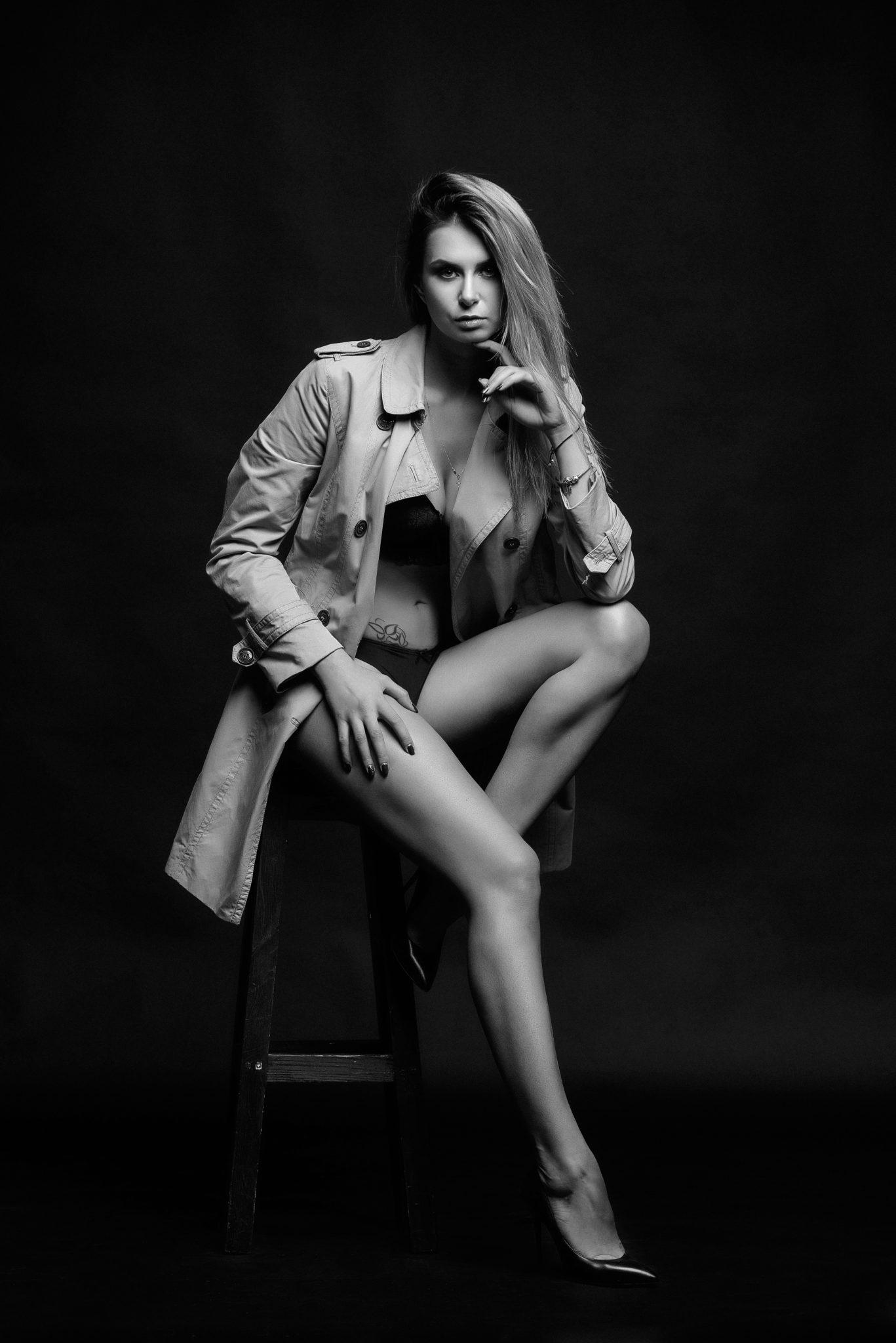 Фотосессия Премиум, чб, модель, девушка в плаще, на черном фоне сидит на стульчике