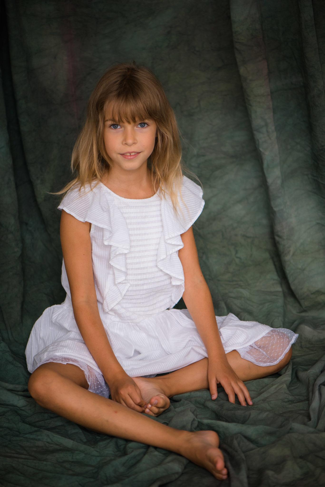 Детская фотосессия, ребенок в белом платье сидит на зеленовом тканевом фоне