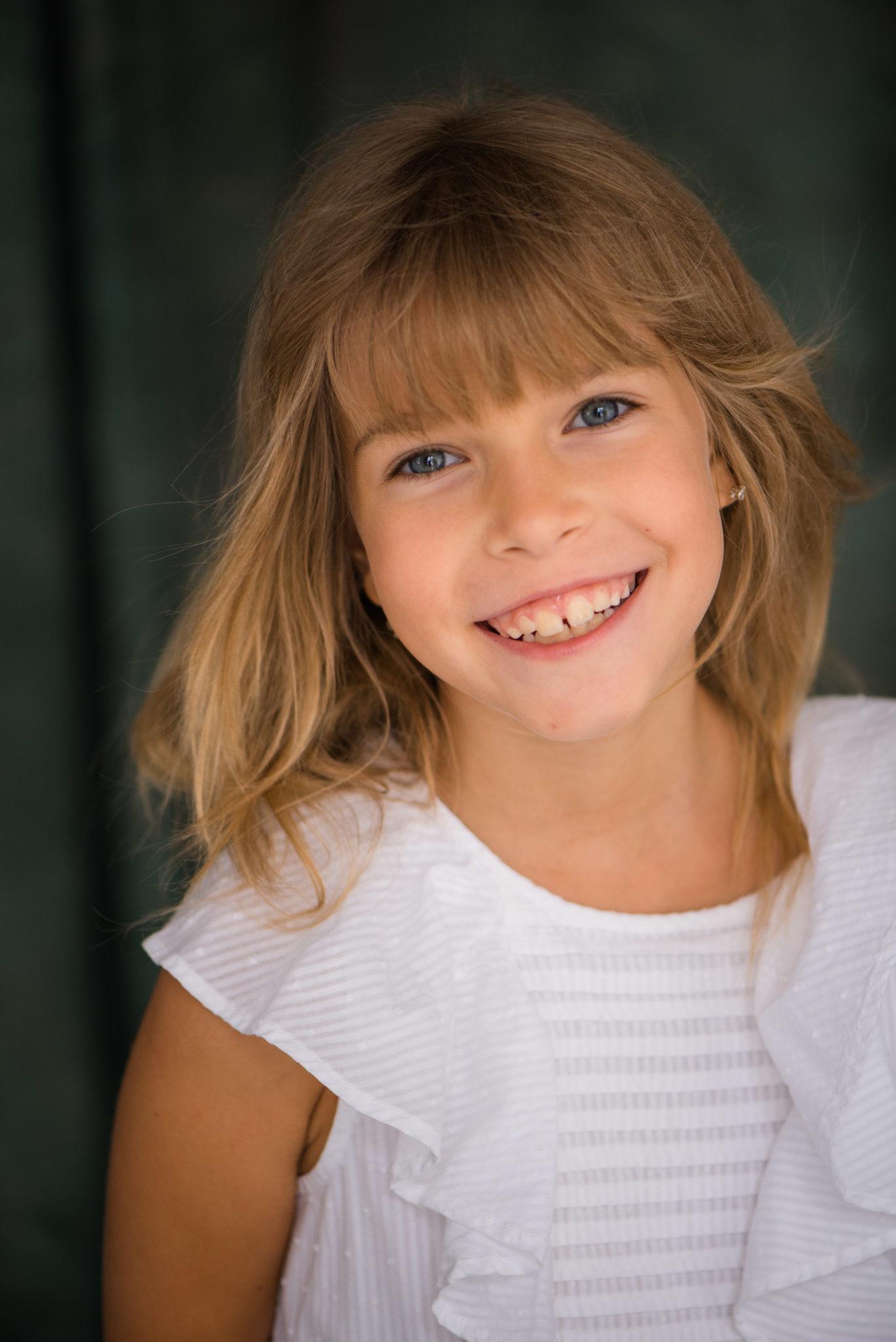 Детская фотосессия, ребенок в белом платье на зеленовом тканевом фоне улыбается в камеру