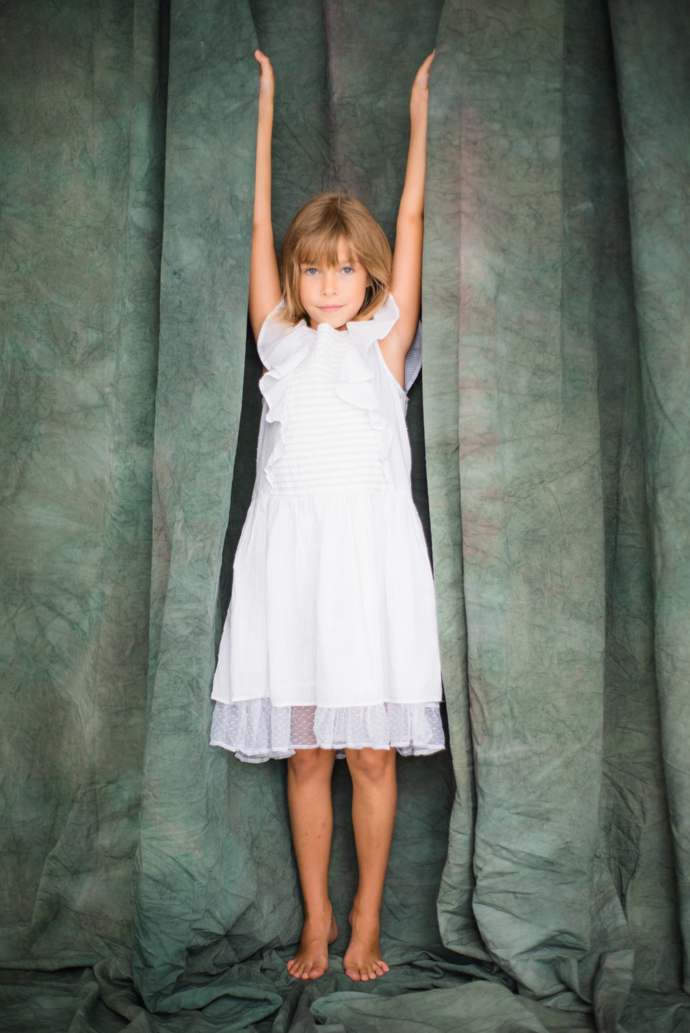 Детская фотосессия, ребенок в белом платье стоит на зеленовом тканевом фоне подняв руки