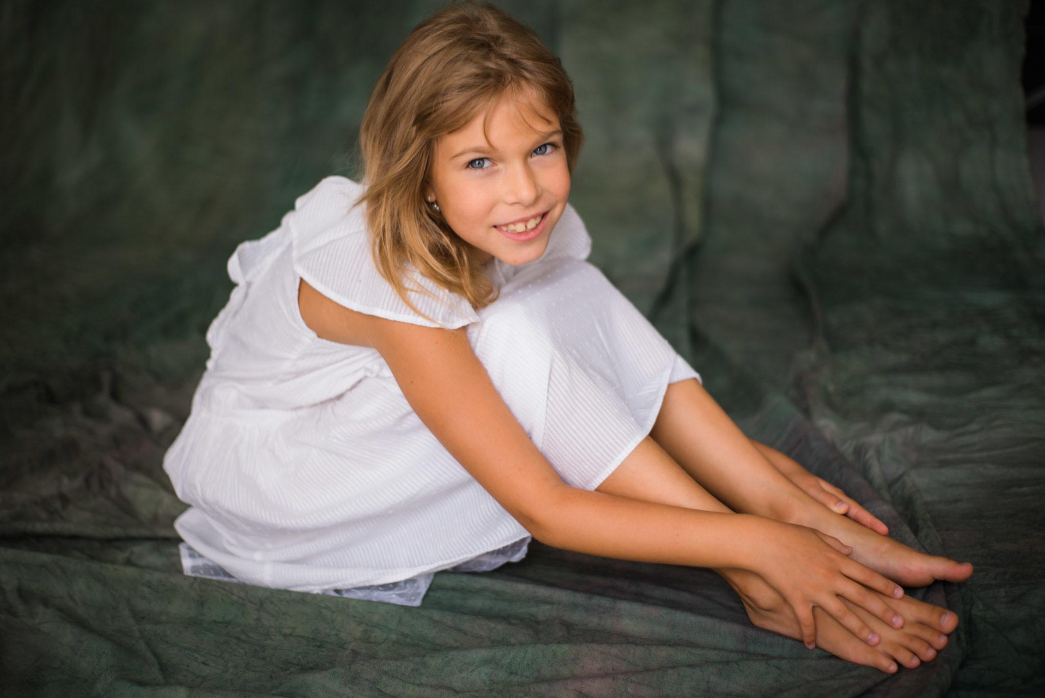 Детская фотосессия, ребенок в белом платье сидит