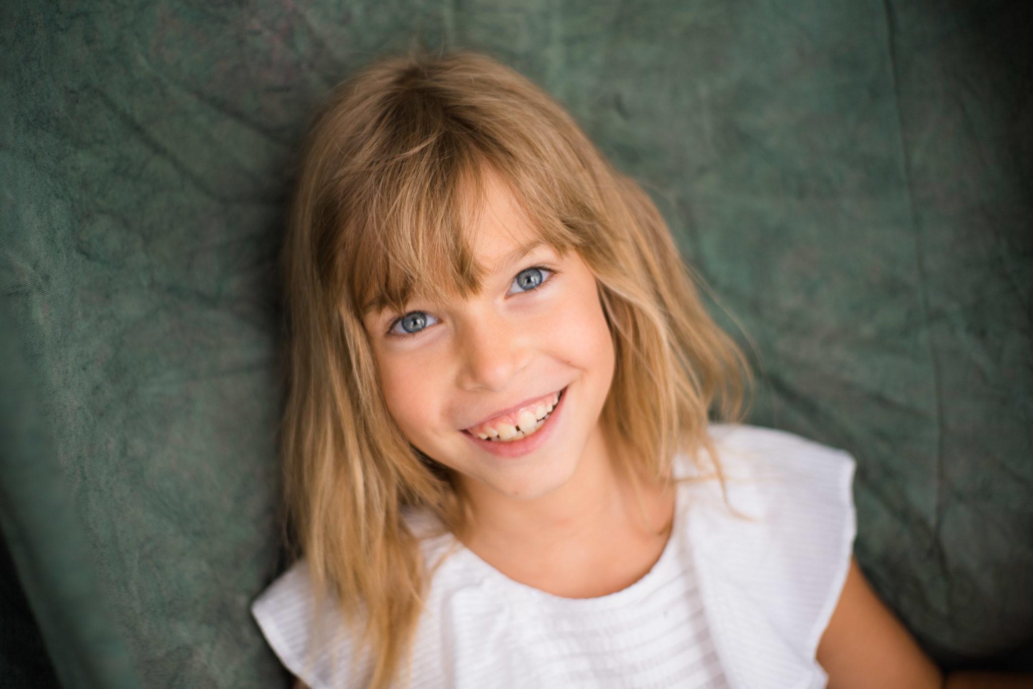 Детская фотосессия, ребенок в белом платье улыбается в камеру, портрет