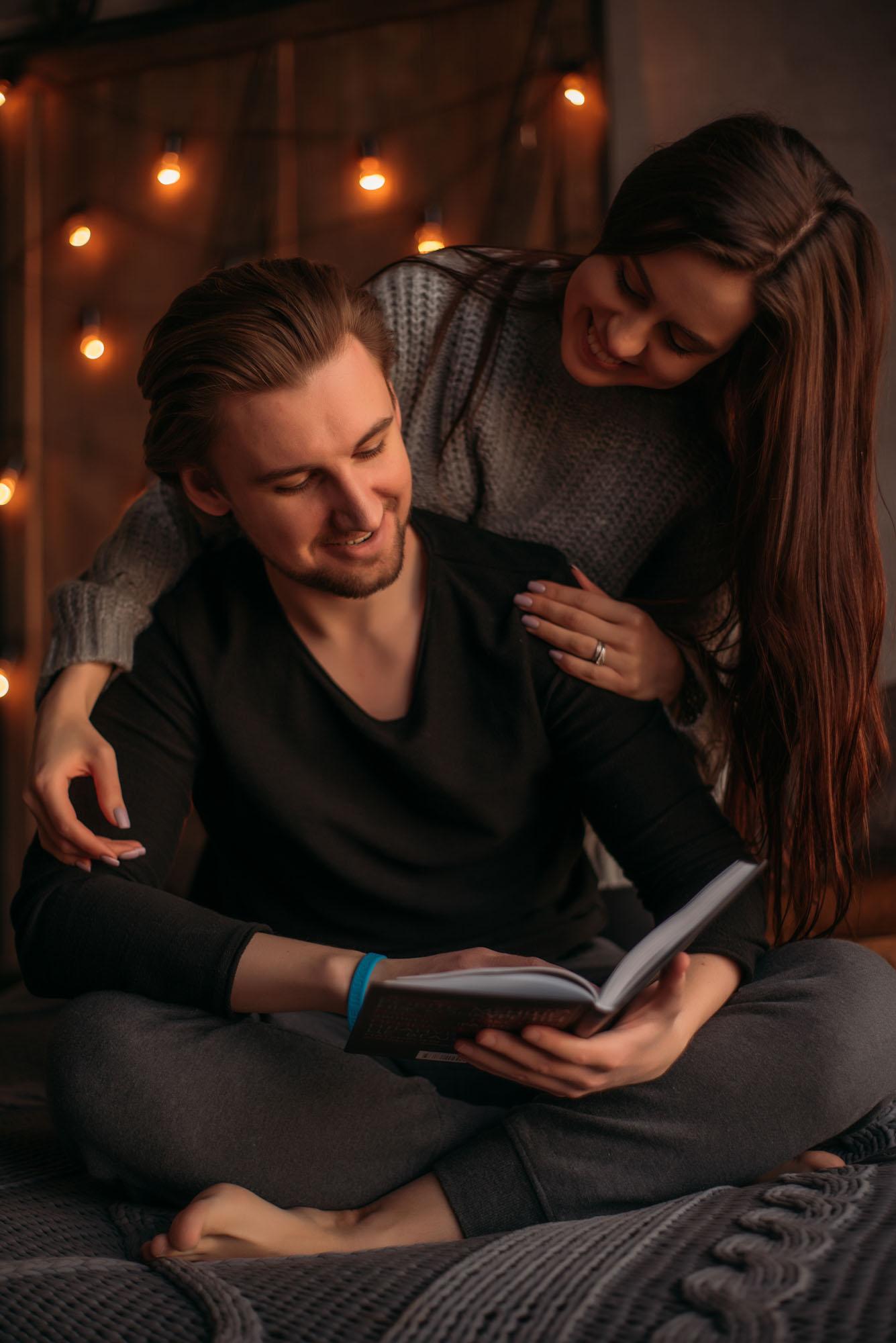 Фотосессия Love Story в студии, девушка и парень читают книгу на кровати