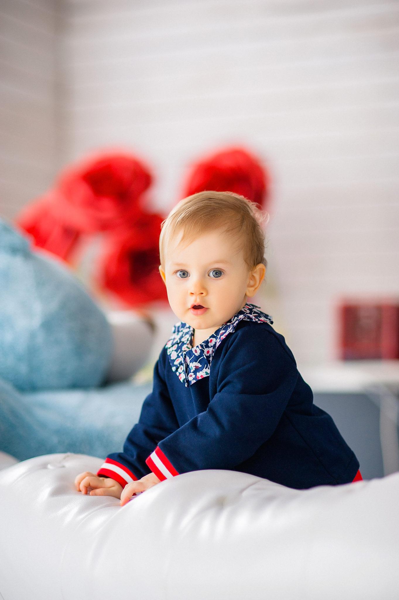 Детская фотосессия, ребенок стоит на белом диване на фоне красных цветов