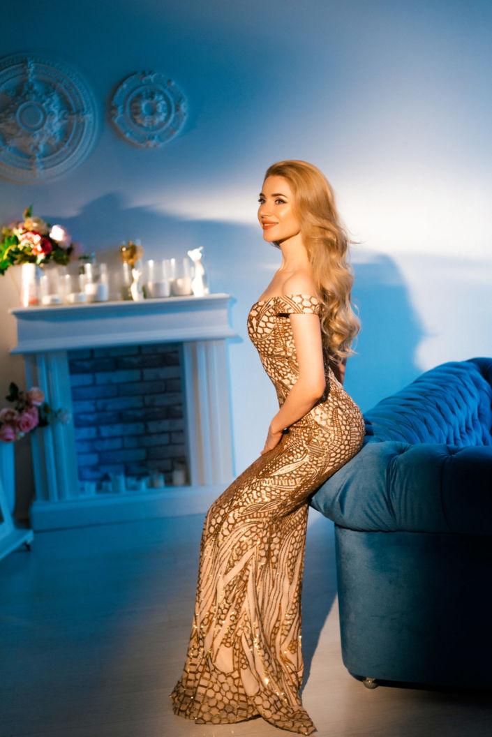 Фотосессия под ключ киев, девушка в золотом платье сидит на диване на фоне камина и белой стены, ph Постникова