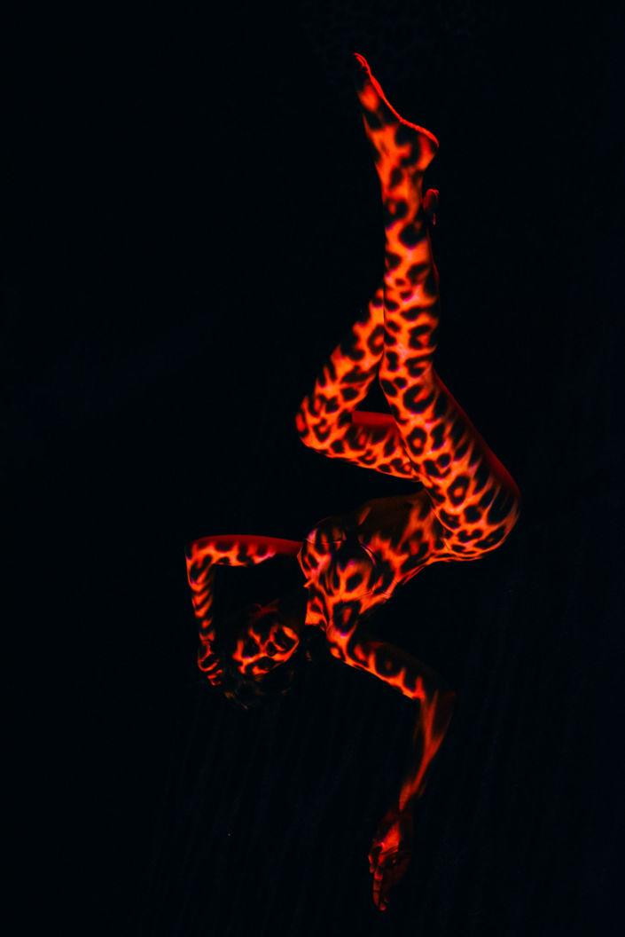 Съемка с проектором, фотосессия с проектором, цвет, девушка лежит на черном фоне, оранжевые пятна