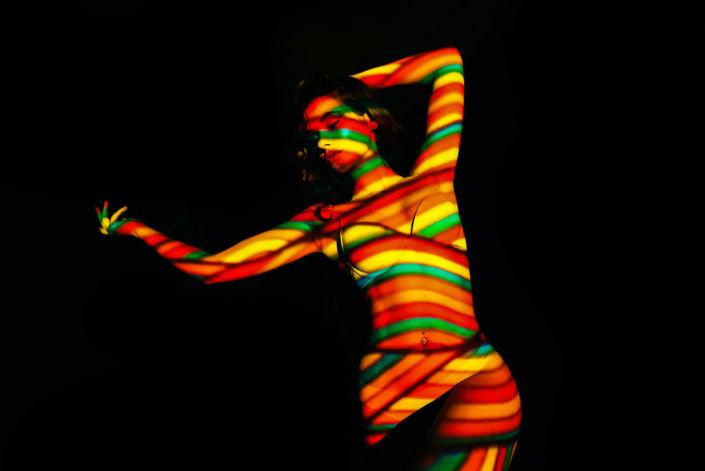 Съемка с проектором, фотосессия с проектором, цвет, девушка лежит на черном фоне, цветные линии