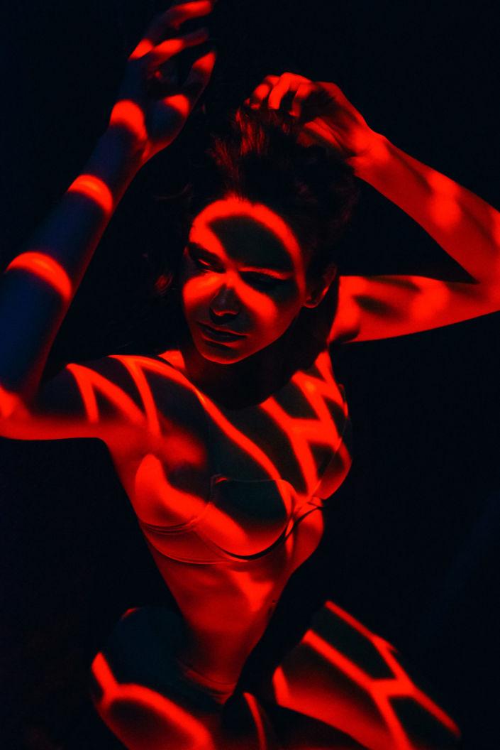 Съемка с проектором, фотосессия с проектором, цвет, девушка лежит на черном фоне, красные оттенки