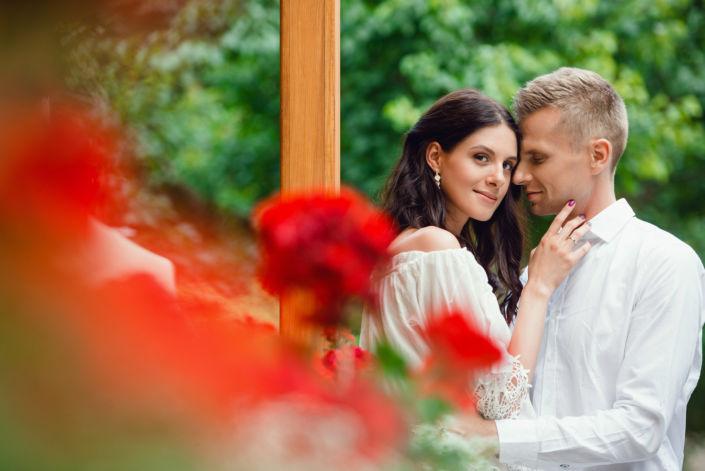 Love Story на природе, на фоне красных цветов