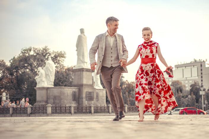 Love story фотосессия, на природе, прогулка по городу, вид на памятник основателям Киева, пара бежит по брусчатке, ph Постникова Алиса