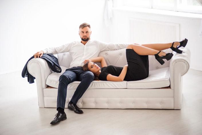 Love story фотосессия, в студии, пара сидит на белом диване на фоне окна