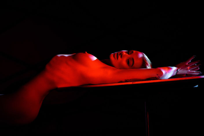 Эротическая фотосессия, фотограф Алиса Постниковой, модель Валерия Ионеску, обнаженная на белом столе спиной, красный свет, цветное фото