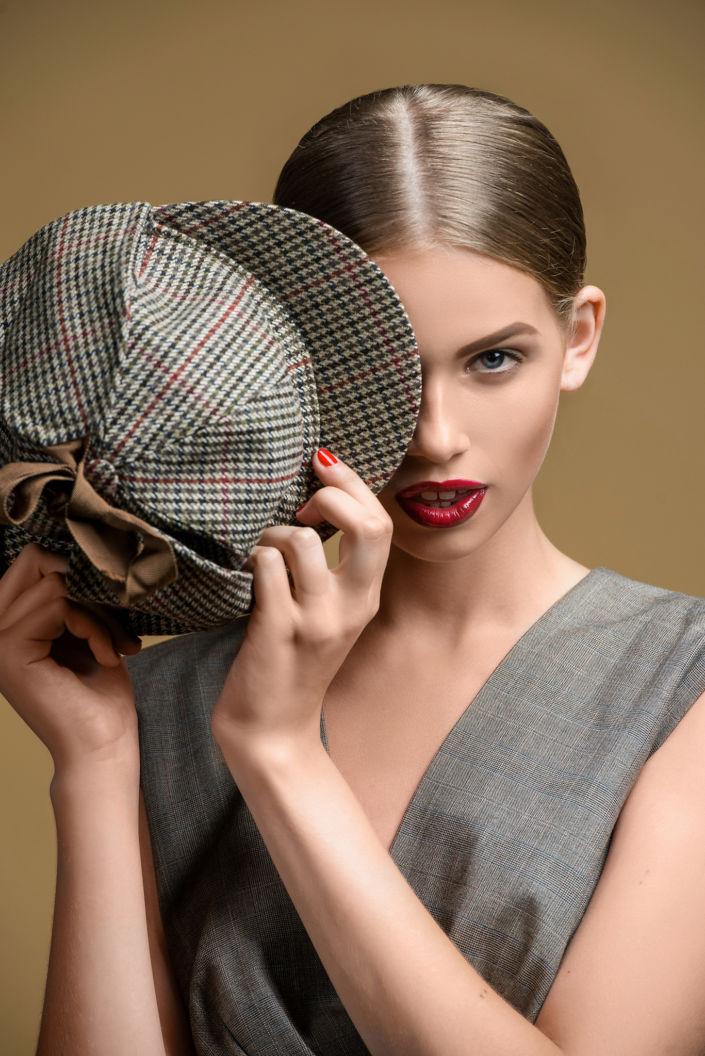 Модельные тесты, девушка с кепкой на коричневом фоне
