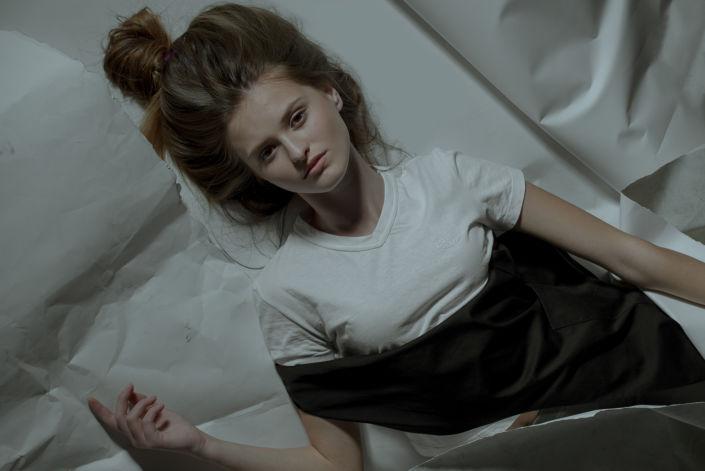 Модельные тесты, чб фото, девушка в белом купальнике лежит на белом рваном фоне