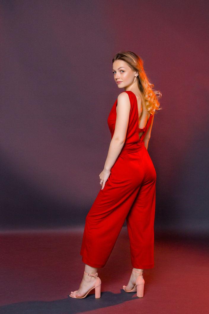Фотосессия мини, девушка в красном комбинезоне на черном фоне