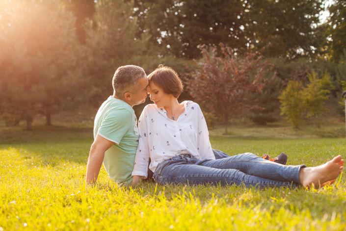Семейная фотосессия на природе, пара сидит на траве в лучах солнца
