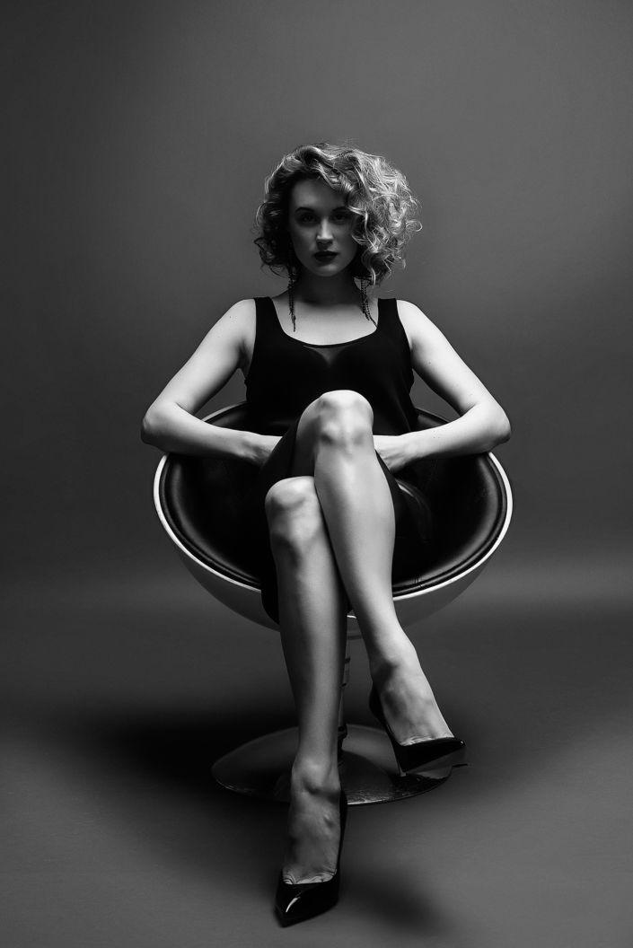 Фотосессия под ключ киев, чб, модель, девушка в платье, на черном фоне сидит в черно-белом кресле