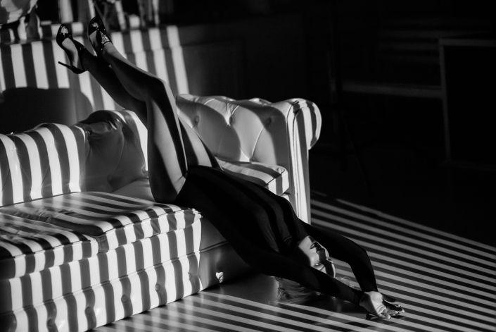 Съемка с проектором, фотосессия с проектором, чб, девушка на белом диване лежит головой в пол